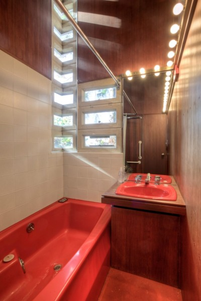 The mitered glass corner windows and the vanity's exposed light-bulbs in the bathroom. Image courtesy of Redfin.