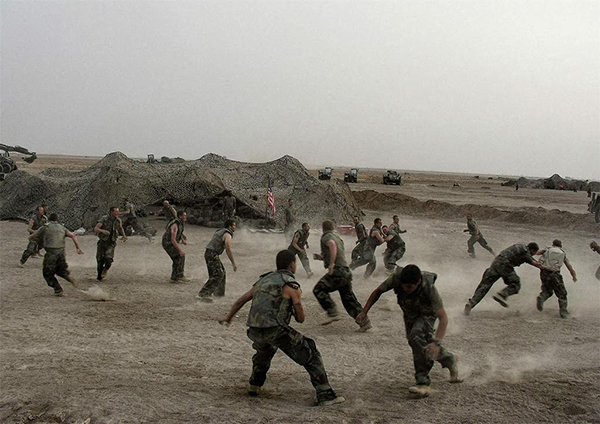 Iraq War, 2003, American soldiers playing football, photograph by Alex Majoli for Magnum Photos. Image courtesy of ARTstor.