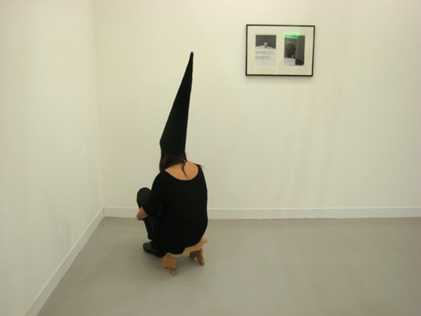 Santiago Sierra, Hooded woman seated facing the wall,  originally performed in the Spanish pavilion at the 2003 Venice Biennale,  re-enacted at New York's Lisson Gallery in 2010. Image courtesy of Metropolis M.
